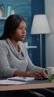 エルを使用してマーケティングオンラインコースで自宅から離れて働いている黒い肌を持つアフリカ系アメリカ人の学生...
