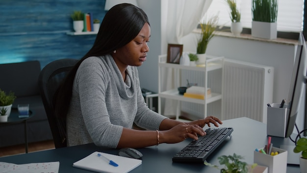 ウェビナー大学のプラットフォームを使用してオンラインコースのマーケティングで自宅から離れて働いている黒い肌を持つアフリカ系アメリカ人の学生
