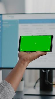 Studente afroamericano che lavora a distanza da casa guardando con schermo verde simulato