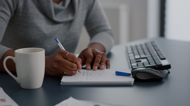 African american student writing high school homework on notebook working remote