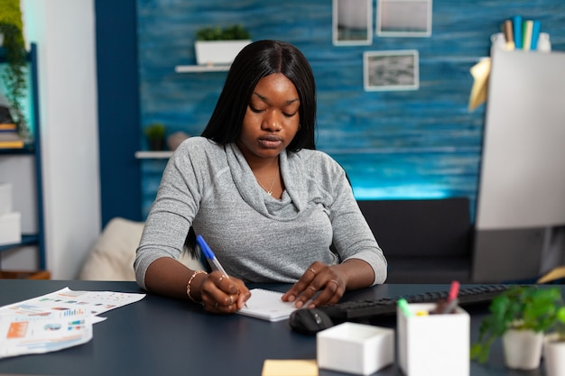 オンラインコミュニケーションコース中にノートに高校の宿題を書いているアフリカ系アメリカ人の学生...