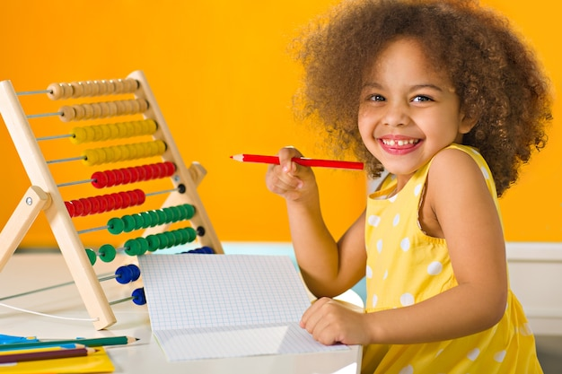 An african american student in a yellow dress laughs brightly near abacus in an elementary school