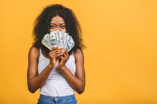 たくさんのお金のドル紙幣を保持しているアフリカ系アメリカ人の成功した女性