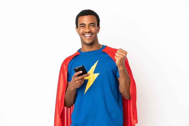 Афро-американский супергерой человек на изолированном белом фоне с телефоном в позиции победы