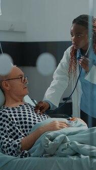 患者に聴診器を使用しているアフリカ系アメリカ人の外科医