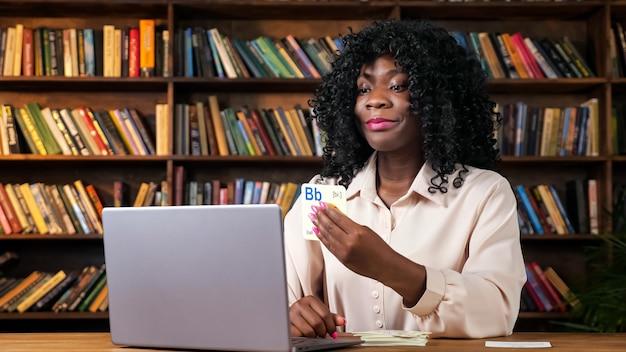 아프리카계 미국인 교사는 집에서 책꽂이에 기대어 테이블에 앉아 온라인 영어 수업에서 노트북 카메라에 편지와 함께 카드를 보여줍니다