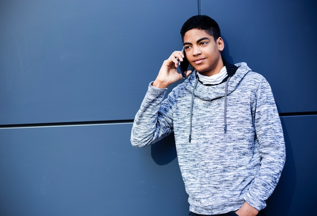 African american teenager boy talking on a mobile phone. y