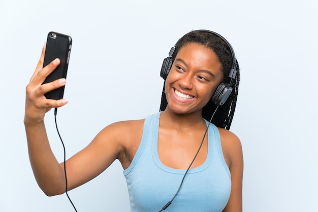 African american teenager girl with long braided hair listening music with a mobile