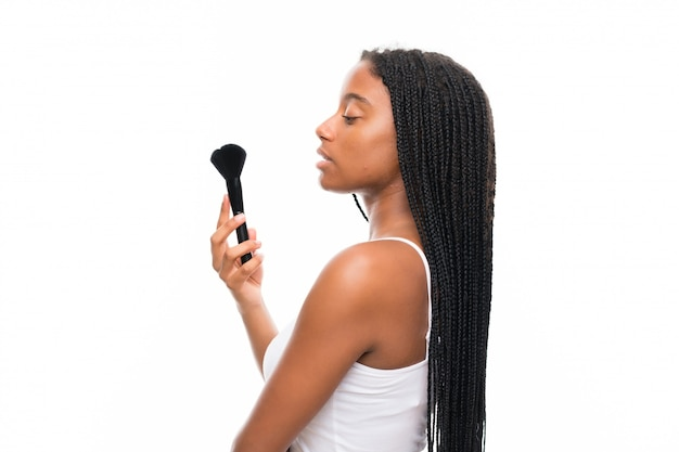 African american teenager girl with long braided hair with makeup brush