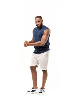 アフリカ系アメリカ人のティーンエイジャーは腕に筋肉を示しています。白い背景で隔離。スタジオポートレート。過渡期の概念