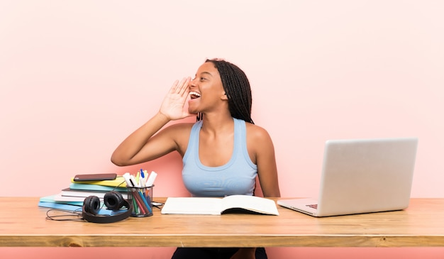 African american teenager student girl with long braided hair in her workplace shouting with mouth wide open to the lateral