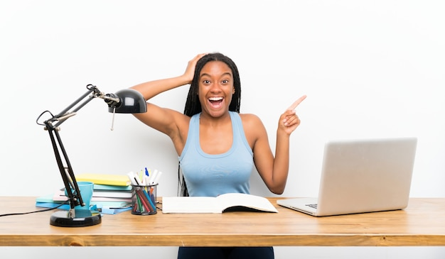 African american teenager student girl with long braided hair in her workplace surprised and pointing finger to the side