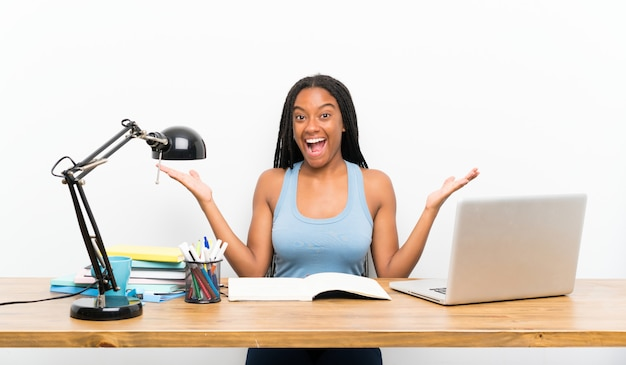 African american teenager student girl with long braided hair in her workplace with shocked facial expression