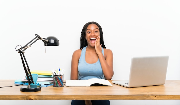 African american teenager student girl with long braided hair in her workplace with surprise and shocked facial expression