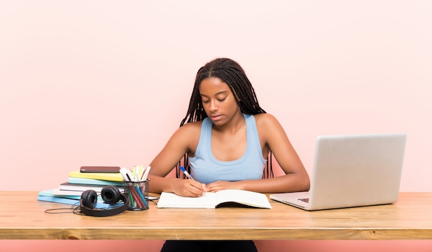African american teenager student girl with long braided hair in her workplace
