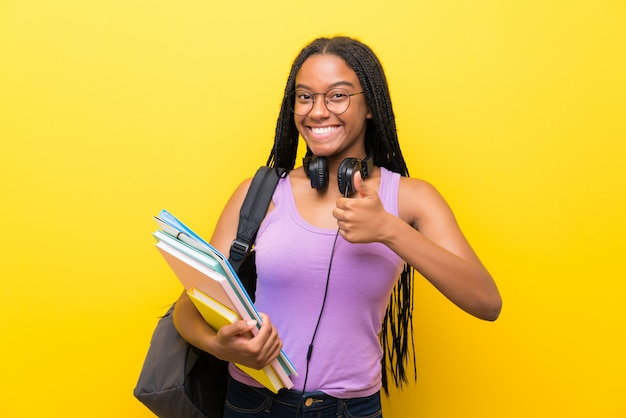 African american teenager student girl with long braided hair over isolated yellow wall giving a thumbs up gesture