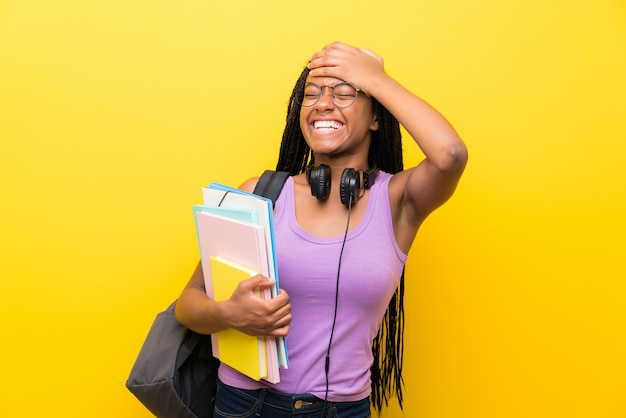African american teenager student girl with long braided hair over isolated yellow wall laughing
