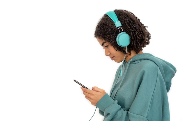 African american teenager in turquoise headphones and in hoodie using smartphone and listening to music