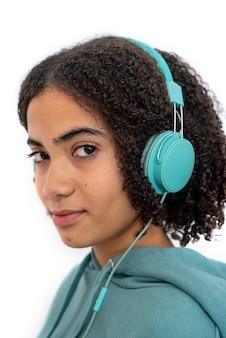 カメラを見て、現代のターコイズブルーのヘッドフォンで音楽を聴いている巻き毛のアフリカ系アメリカ人のティーンエイジャー