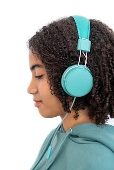 現代のターコイズブルーのヘッドフォンで見下ろし、音楽を聴いている巻き毛のアフリカ系アメリカ人のティーンエイジャー