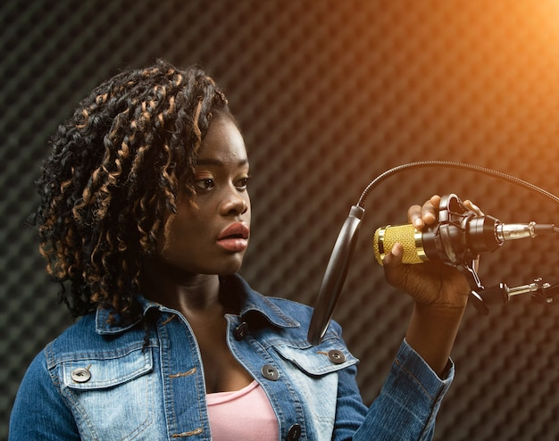 African american teenager woman afro hair sing a song loudly with power sound over hanging microphone condenser jean jacket. egg crate studio low lighting shadow sound proof absorbing wall room