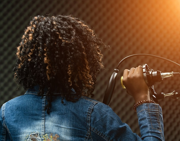 African american teenager woman afro hair sing a song loudly with power sound over hanging microphone condenser jean jacket. egg crate studio shadow sound proof absorbing wall room, back side view