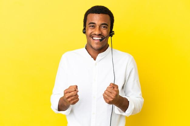 勝者の位置での勝利を祝う孤立した黄色の背景の上にヘッドセットで作業しているアフリカ系アメリカ人のテレマーケティングの男