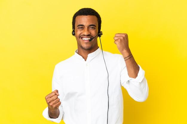 勝利を祝う孤立した黄色の背景の上にヘッドセットで作業しているアフリカ系アメリカ人のテレマーケターの男