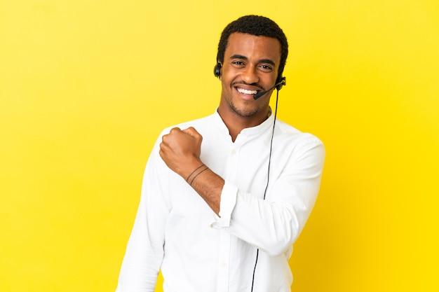 勝利を祝う孤立した黄色の背景の上にヘッドセットで作業しているアフリカ系アメリカ人のテレマーケティングの男