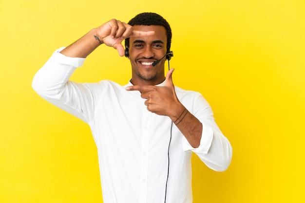 孤立した黄色の背景に焦点を当てた顔の上にヘッドセットで作業しているアフリカ系アメリカ人のテレマーケティングの男。フレーミングシンボル
