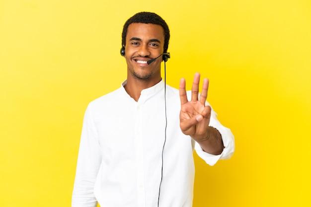 고립된 노란색 배경 위에 헤드셋을 사용하는 아프리카계 미국인 텔레마케터 남자는 행복하고 손가락으로 세 개를 세고 있습니다.