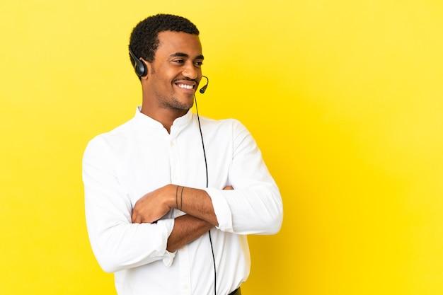 고립된 노란색 배경 위에 헤드셋을 사용하고 행복하고 웃고 있는 아프리카계 미국인 텔레마케터