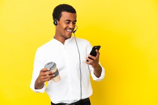아프리카계 미국인 텔레마케터 남자는 테이크아웃 커피와 모바일을 들고 고립된 노란색 배경 위에 헤드셋을 사용합니다.