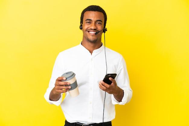 持ち帰り用のコーヒーと携帯電話を保持している孤立した黄色の背景の上にヘッドセットで作業しているアフリカ系アメリカ人のテレマーケティングの男