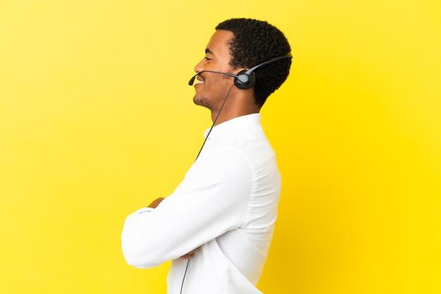측면 위치에서 고립 된 노란색 배경 위에 헤드셋으로 작업 하는 아프리카 계 미국인 텔레마케터 남자