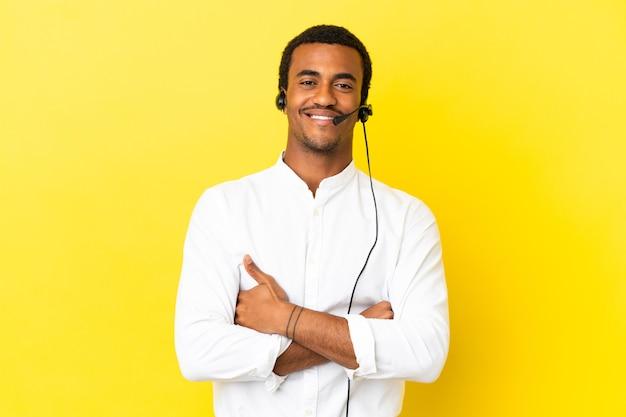 腕を正面の位置で交差させたまま、孤立した黄色の背景の上にヘッドセットで作業しているアフリカ系アメリカ人のテレマーケティングの男