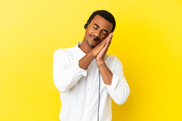 아프리카계 미국인 텔레마케터 남자는 격리된 노란색 배경 위에 헤드셋을 사용하여 사랑스러운 표정으로 수면 제스처를 취합니다.