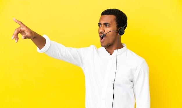 멀리 가리키는 고립 된 노란색 배경 위에 헤드셋으로 작업 하는 아프리카 계 미국인 텔레마케터 남자