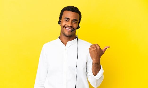 제품을 제시하기 위해 측면을 가리키는 고립된 노란색 배경 위에 헤드셋을 사용하는 아프리카계 미국인 텔레마케터