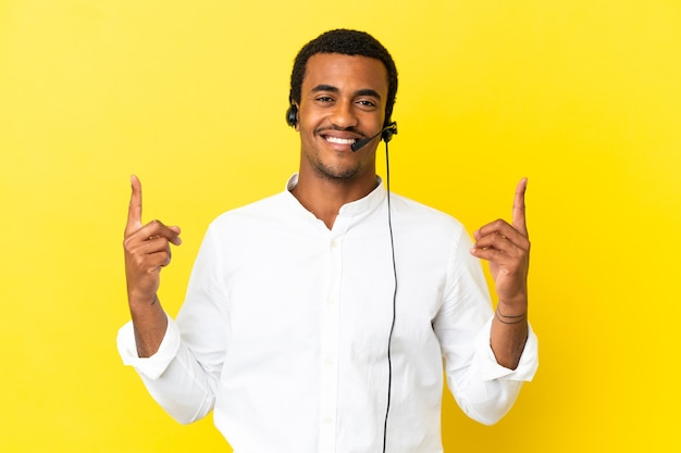 아프리카계 미국인 텔레마케터 남자는 고립된 노란색 배경 위에 헤드셋을 사용하여 훌륭한 아이디어를 가리키고 있습니다.
