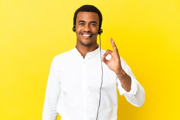 아프리카계 미국인 텔레마케터 남자는 고립된 노란색 배경 위에 헤드셋을 사용하여 손가락으로 확인 표시를 하고 있습니다.
