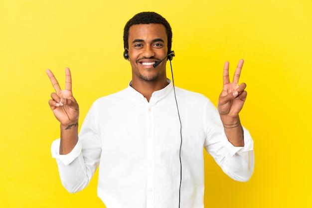 두 손으로 승리 표시를 보여주는 고립 된 노란색 배경 위에 헤드셋으로 작업 하는 아프리카 계 미국인 텔레마케터 남자