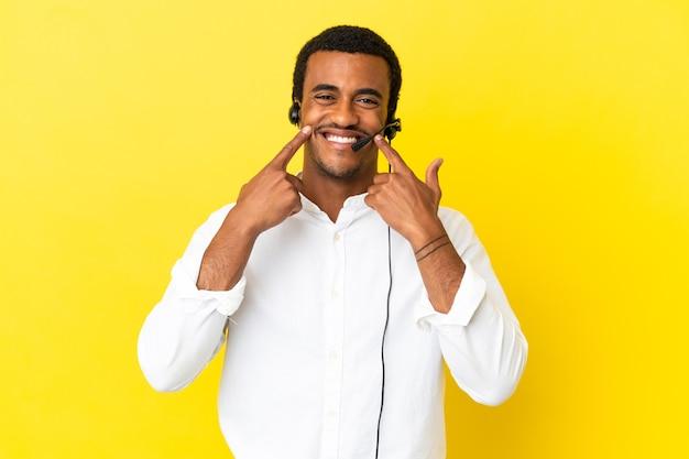 행복하고 즐거운 표정으로 웃고 있는 고립된 노란색 배경 위에 헤드셋을 사용하는 아프리카계 미국인 텔레마케터