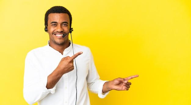 孤立した黄色の背景の上にヘッドセットで作業しているアフリカ系アメリカ人のテレマーケティングの男は驚いて、側を指しています