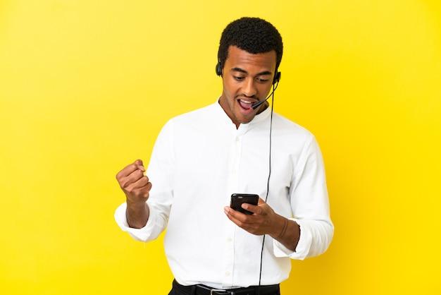 孤立した黄色の背景の上にヘッドセットを操作して驚いてメッセージを送信するアフリカ系アメリカ人のテレマーケティングの男