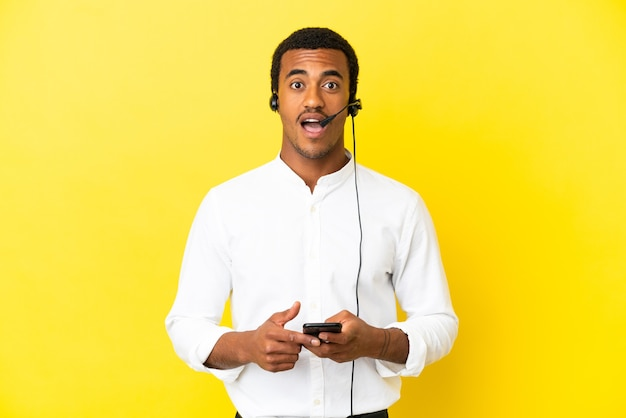 Афро-американский телемаркетер человек, работающий с гарнитурой на изолированном желтом фоне, удивлен и отправляет сообщение