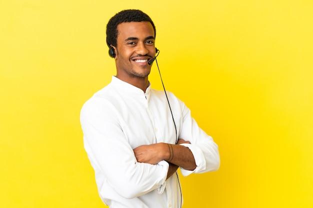 腕を組んで、楽しみにして孤立した黄色の背景の上にヘッドセットで作業しているアフリカ系アメリカ人のテレマーケティングの男
