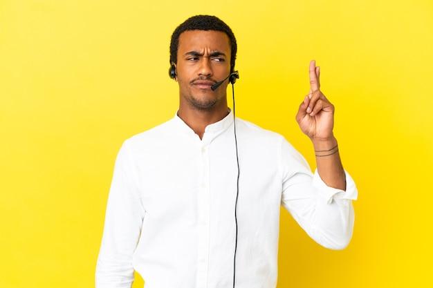 아프리카계 미국인 텔레마케터 남자는 고립된 노란색 배경에서 헤드셋을 사용하고 손가락을 교차하고 최고를 기원합니다.