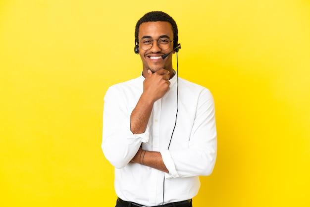 Афро-американский телемаркетер человек, работающий с гарнитурой на изолированном желтом фоне в очках и счастливый