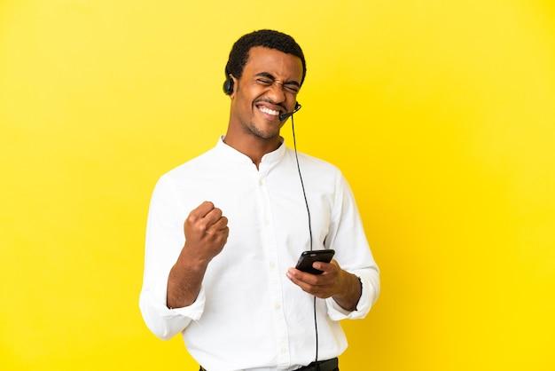 승리 위치에 전화와 격리 된 노란색 배경 위에 헤드셋으로 작업 하는 아프리카 계 미국인 텔레마케터 남자